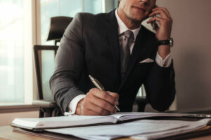 Businessman talking on mobile phone while working at his desk.